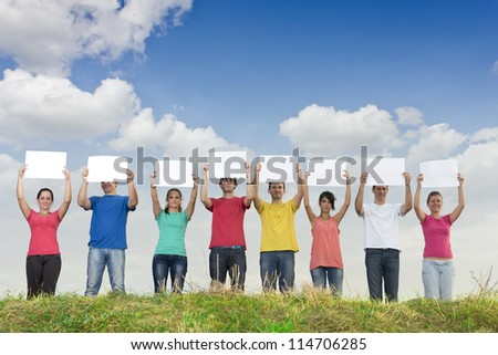 Group of young people holding blank papers in nature - stock photo