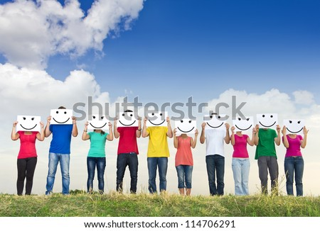 Group of young people holding papers with smileys in front of their faces - stock photo