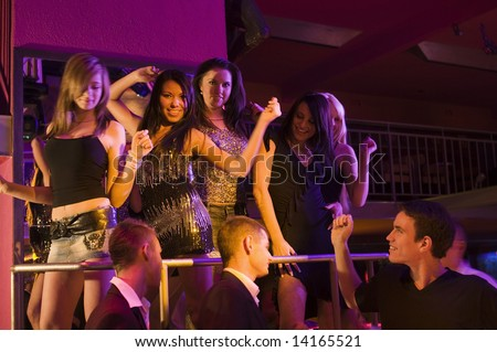 group of young people in a disco night club dancing - stock photo