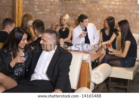 group of young people in a pub drinking and chatting focus on the couple - stock photo