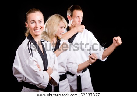 Group of young people in kimono in martial arts training and exercising taekwondo in gym over black background. - stock photo