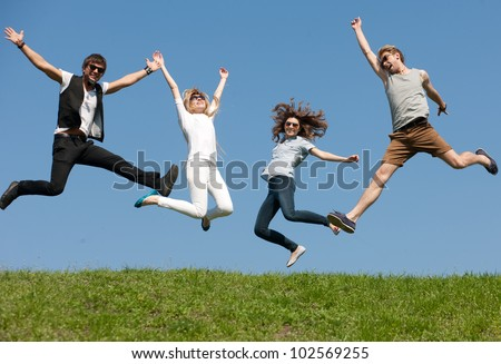Group of young people jump across blue sky - stock photo