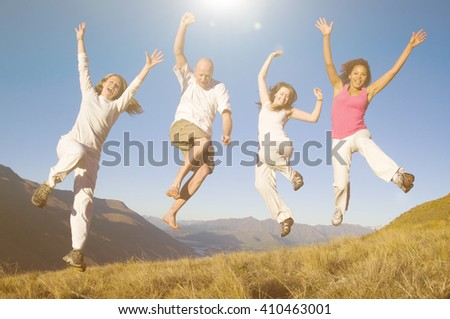 Group of young people jumping in the field.