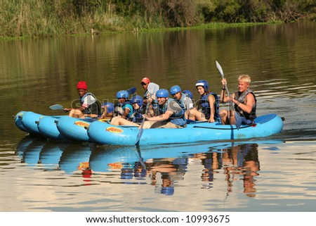 group of young people kayaking along tranquil river as teambuilding excercise - stock photo
