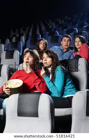 Group of young people look a film at a cinema - stock photo