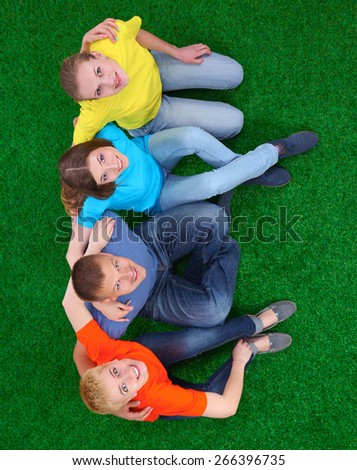 Group of young  people lying on green grass . - stock photo