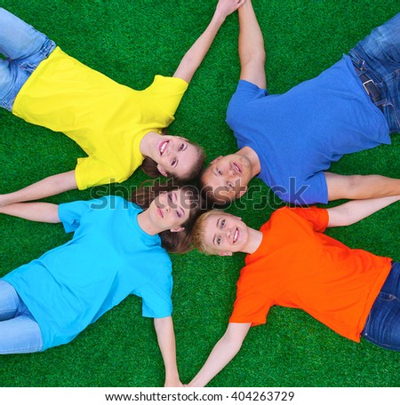 Group of young  people lying on green grass  - stock photo