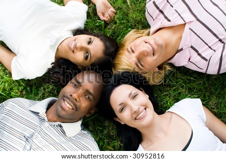 group of young people or college students lying on grass - stock photo