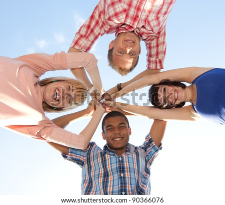 Group of young people outdoor hug each other across blue sky - stock photo