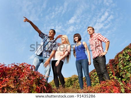 Group of young people outdoor rise up hands across blue sky