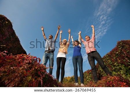 Group of young people outdoor rise up hands acrosss blue sky - stock photo