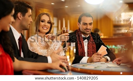 Group of young people playing poker in a casino - stock photo