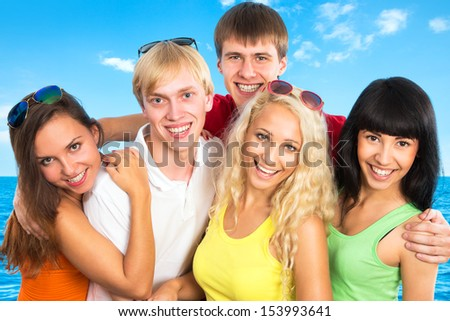 Group of young people pose at the beach of sea - stock photo
