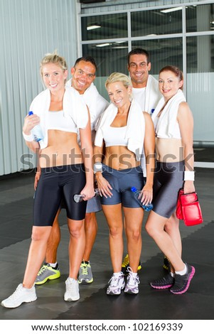 group of young people relaxing after workout in gym