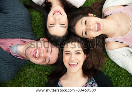 Group of young people relaxing and lying on the grass - stock photo