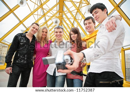 group of young people removes itself to video camera on footbridge - stock photo