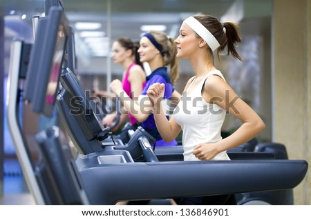 group of young people running on treadmill in gym - stock photo