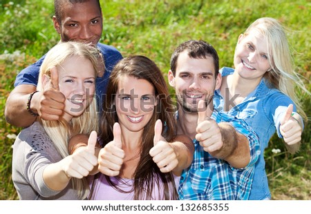 Group of young people showing thumbs up. - stock photo