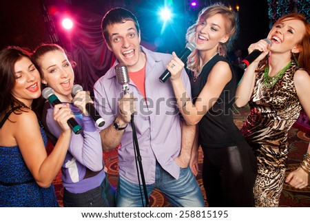 group of young people singing into  microphone at  party. karaoke - stock photo