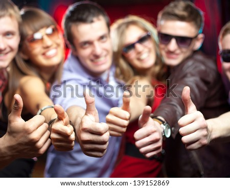 group of young people singing shows gesture OK at a party. - stock photo