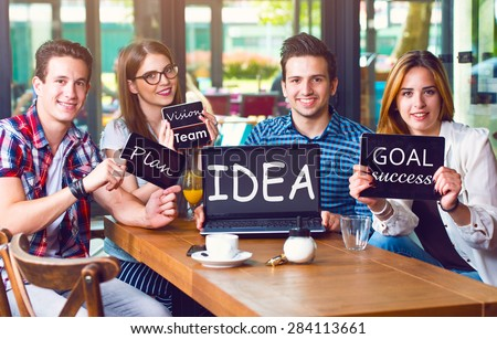 Group of young people sitting at a cafe, holding electronic gadgets with messages - stock photo