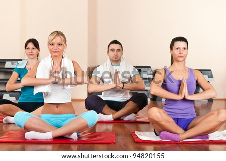 group of young people  sitting cross-legged on mat and meditating - stock photo