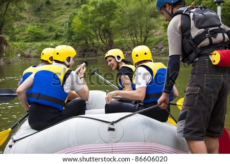 Group of young people sitting in a boat, getting ready for whitewater rafting - stock photo