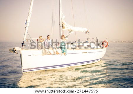 Group of young people sitting on a sailing boat - Two beautiful women and attractive man having fun on a boat while on vacation - Rich people enjoying party - stock photo