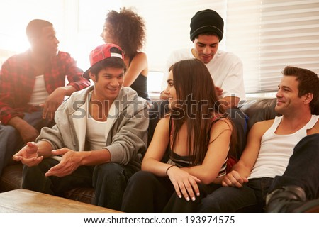 Group Of Young People Sitting On Sofa And Talking - stock photo