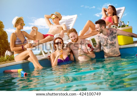 Group of young people spend hot summer at swimming pool with cold drinks