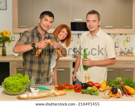 group of young people standing and having fun in kitchen, preparing food - stock photo