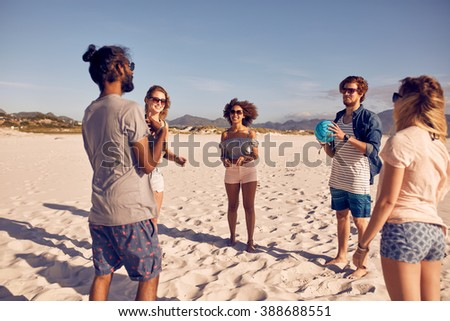 Group of young people standing in circle on the beach and playing with ball. Young friends playing ball game on a sandy beach. - stock photo