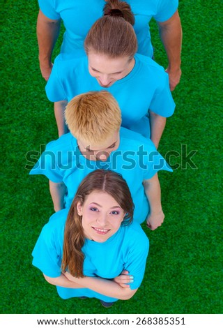 Group of young  people standing on green grass . - stock photo