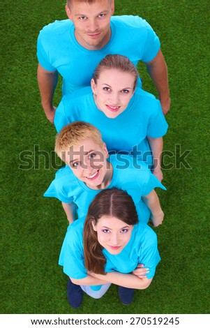 Group of young  people standing on green grass .