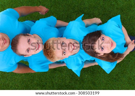 Group of young  people standing on green grass  - stock photo