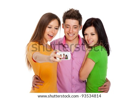 Group of young people taking a self portrait with their phone, happy smiling students friends standing isolated on white background - stock photo