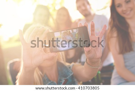 Group of young people taking a selfie outdoors, having fun - stock photo