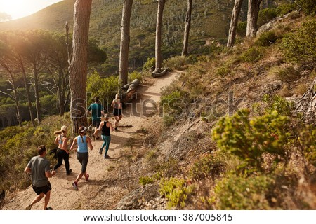 Group of young people trail running on a mountain path. Runners working out in beautiful nature. - stock photo