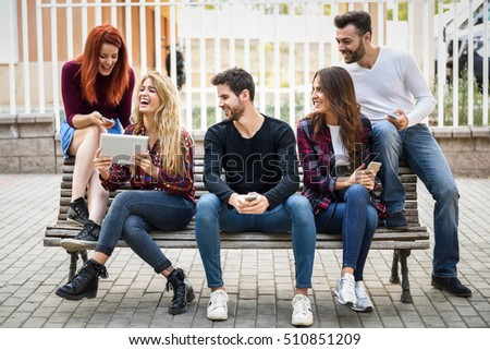 Group of young people using smartphone and tablet computers outdoors in urban background. Women and men sitting on a bench in the street wearing casual clothes.