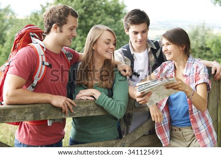 Group Of Young People Walking In Countryside - stock photo