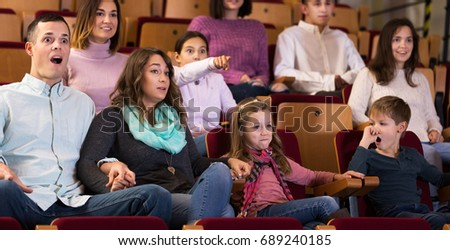 Group of young people watching exciting movie in cinema house indoors