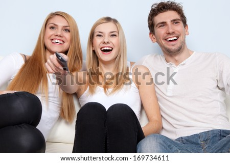 Group of young people watching tv at home - stock photo