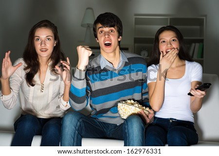 group of young people watching TV on the couch, sports fans