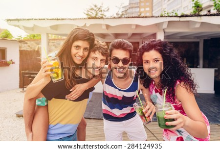 Group of young people with healthy drinks having fun in a summer party - stock photo
