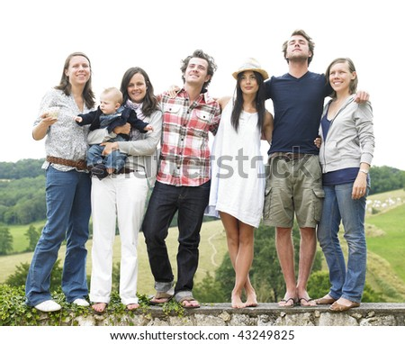 Group of young people, with one woman holding a baby, standing on a stone wall outdoors. Horizontal. - stock photo