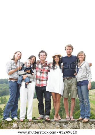 Group of young people, with one woman holding a baby, standing on a stone wall outdoors. Vertical. - stock photo