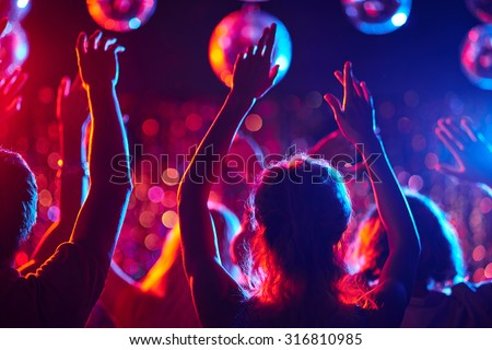 Group of young people with raised arms dancing in night club - stock photo