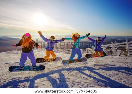 Group of young people with snowboard on ski holiday in mountains - stock photo