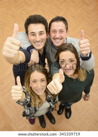 Group of young people with thumbs up - stock photo