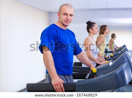 Group of young people working on the treadmill at the gym. Portrait of an athletic young man in the foreground